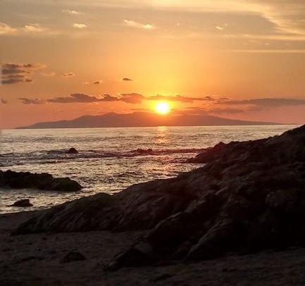 海岸で夕日が沈む
